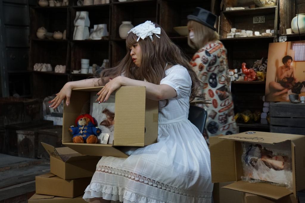 在【真人性愛娃娃】ほたる身後的是在會場尋找各種道具佈置娃娃的新レイヤ